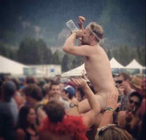 Потный, пьяный парень без рубашки в толпе.