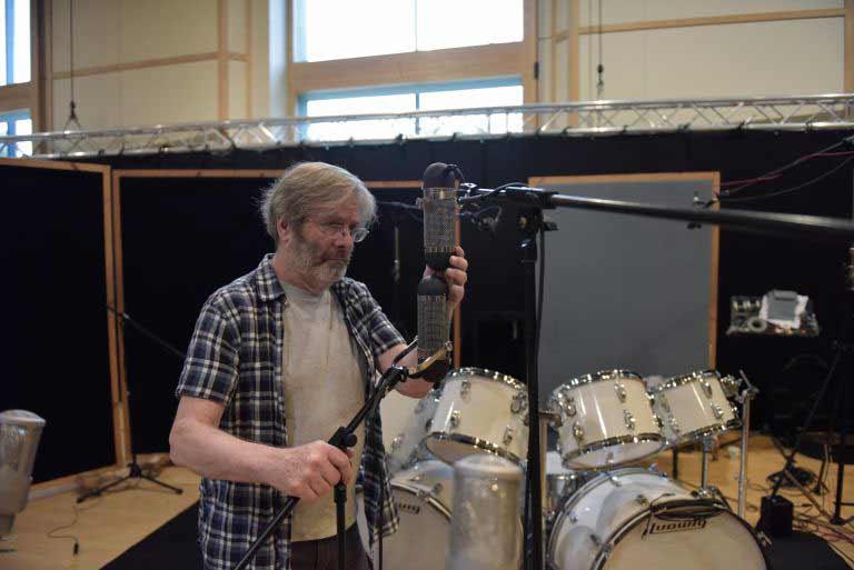 Легендарный звукорежиссер, аудио-пионер и изобретатель Джордж Массенбург настраивает пару микрофонов для записи нескольких барабанов в Galaxy Studios, Бельгия.